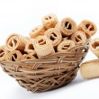 Foto de Stock  : Crispy cinnamon rolls in basket on white background.