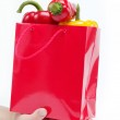 Fresh vegetables. Red gift bag in the women's hands on a white b — Stock Photo