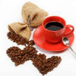 Heart made ​​from coffee beans around cup of coffee on w — Stock Photo #9593571