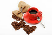 Heart made from coffee beans around a cup of coffee on a w — Stock Photo