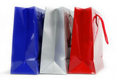 Red, blue and gray gift bags on a white background. — Stock Photo