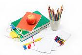 School supplies: books, notebook, pens, pencils, an apple on a w — Stockfoto