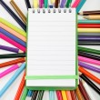 Notepad on a background of colored pencils. - Stock Photo