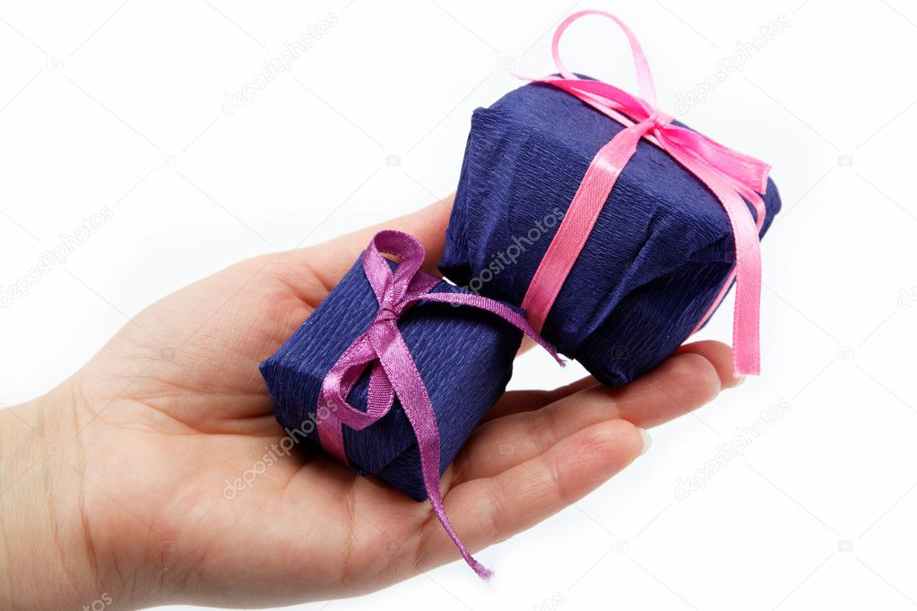 Gift pack in the women's hand on a white background. — Stock Photo #9920846