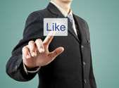Businessman hand pushing Like button — Stock Photo