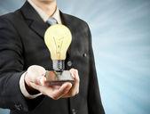 Affärsman håller mobiltelefon glödlampa kommer ut tek — Stockfoto