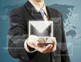 Businessman holding mobile phone and mail — Stock Photo