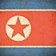 Foto de Stock  : Old grunge paper with North Korea flag background