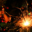 Christmas tree decorations and burning sparkler — Stock Photo