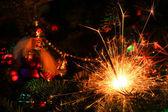 Christmas tree decorations and burning sparkler — Stock Photo