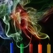 Extinguished candles with colorful smoke on black — Stock fotografie
