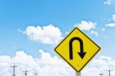 U-turn symbol and blue sky — Stock Photo