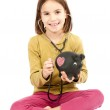 Little girl with stethoscope and piggy bank — Stock Photo #8763016