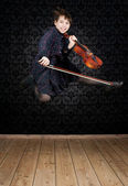 Young girl with violin jumping — Stock Photo