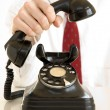 Holding an old black telephone — Stock Photo