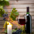 Red wine bottle with a candle — Stock Photo
