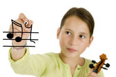 Young girl writing with a pen and holding a violin — Stock Photo