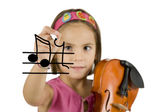 Little girl writing with a pen and holding a violin — Stock Photo