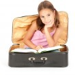 Little girl inside a suitcase reading a book — Stock Photo