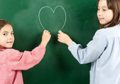 Two girls with blackboard — Stock Photo