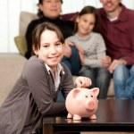 Young girl saving money on a piggy bank — Stock Photo