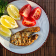 Fried fish in batter served with tomatoes — Stock Photo