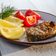 Fried fish served with tomatoes and lemon — Stock Photo