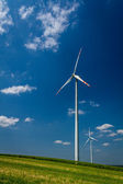 Wind Turbines on green field with blue sky — Stock Photo