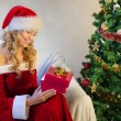 Young woman surprise when opening christmas present — Stock Photo