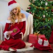 Stock Photo: Christmas gift, tree and beautiful young womin red