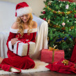 Beautiful woman in red unpack christmas gift — Stock Photo