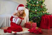 Beautiful woman in red enjoying christmas present — Stock Photo