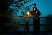Man on old bridge with scythe and oil lamp — Stock Photo
