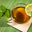 Hot cup of tea with lemon on bamboo mat — Stock Photo