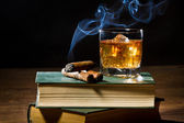 Cigar with blue smoke and whisky on ice and two books volume — Stock Photo