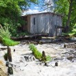 Stock Photo: Old broken mill near river in summer