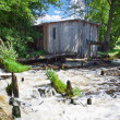 Old broken mill near river in summer - Stock Photo