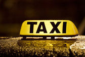 Taxi sign in rainy day — Stock Photo