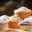 Sprinkling caster sugar on some muffins — Stock Photo