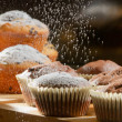 Falling caster sugar on various muffins - Stock Photo