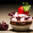 Muffin with strawberry and petals rose - Stock Photo