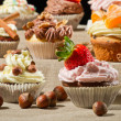 Various muffins with cream, fruits and nuts - Stock Photo