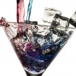Poured red and blue liqueur in a glass with ice cubes on white b — Stock Photo #9715747