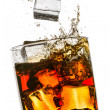 Splash in a glass of whiskey on white background - Stock Photo