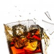 Ice cubes breaking whisky glass filled with bourbon on white bac - Stock Photo