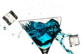 Ice cubes breaking martini glass filled with blue liqueur on whi — Stock Photo