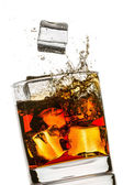 Splash in a glass of whiskey on white background — Stock Photo