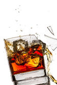 Ice cubes breaking whisky glass filled with bourbon on white bac — Stock Photo