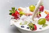 Fresh fruits and milk splash — Stock Photo
