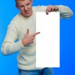 Handsome young man holding big white blank — Stock Photo #8007117